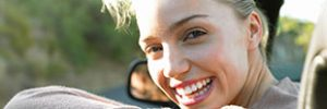 Woman happily leaning her head out of the window of a new convertible