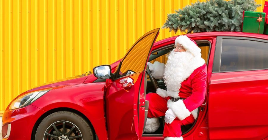 Santa getting out of a red car with a Christmas tree on the roof