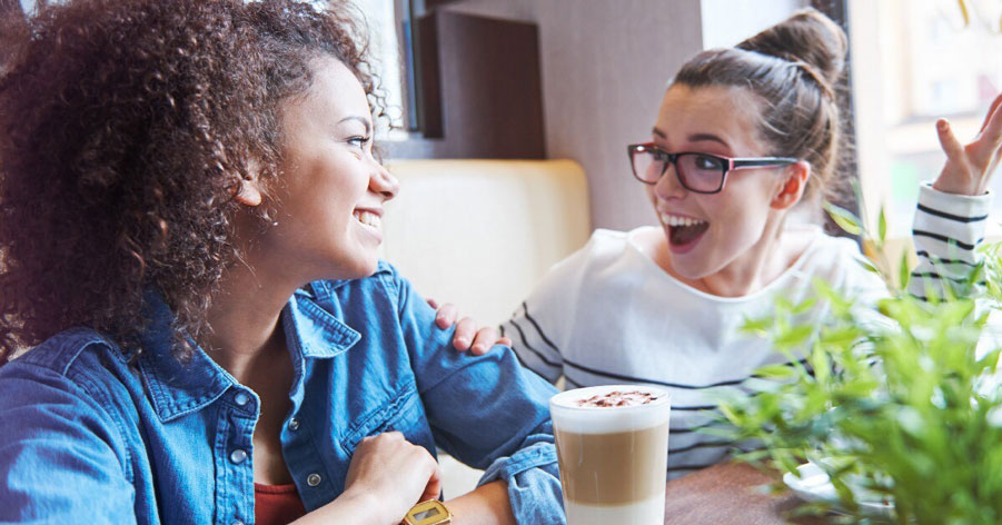Friends sharing an exciting conversation over a cup of coffee