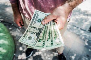 economic impact statements image man holding twenty dollar bills